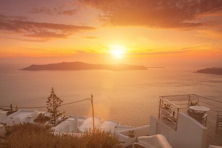 Sunset overlooking the caldera and the sea in the village of Imerovigli on the island of Santorini in the summer. Greece. White roof on a foreground.