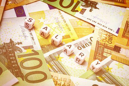 """Beaded inscription """"salary"""" and euro notes."""