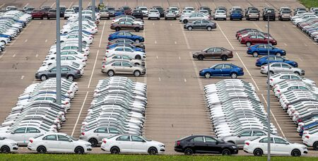 Rows of a new cars parked in a distribution center on a cloudy day in the spring, a car factory. Top view to the parking in the open air.