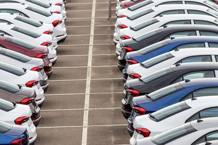 Rows of a new cars parked in a distribution center of a car factory. Top view to the parking in the open air.