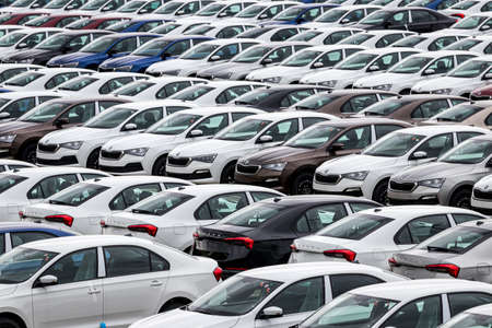 Volkswagen Group Rus, Russia, Kaluga - MAY 24, 2020: Rows of a new cars parked in a distribution center on a cloudy day in the spring, a car factory. Parking in the open air.