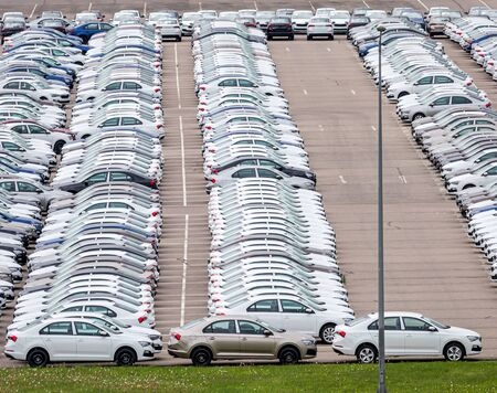Rows of a new cars parked in a distribution center on a car factory on a cloudy day. Top view to the parking in the open air. Standard-Bild