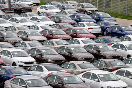 Volkswagen Group Rus, Russia, Kaluga - MAY 24, 2020: Rows of a new cars parked in a distribution center. Top view to the parking in the open air.