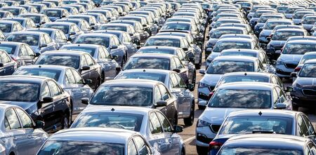 Rows of a new cars parked in a distribution center on a car factory on a sunny day. Parking in the open air.