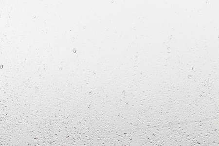 Rain drops on window glasses surface with gray sky background. Natural backdrop of raindrops. Abstract overlay for design. The concept of bad rainy weather.