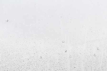 Rain drops on window glasses surface with gray sky background. Natural backdrop of raindrops. Abstract overlay for design. The concept of bad rainy weather. Stockfoto