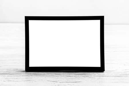 White wooden floor over concrete or decorative plaster wall and black photo frame with copy space for a text background. Mock up for design.