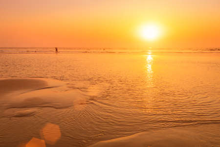 A colorful sunset or sunrise on the seaside with a sandy beach with impurities of volcanic ash. Mandrem, Goa, India. Beautiful seascape.