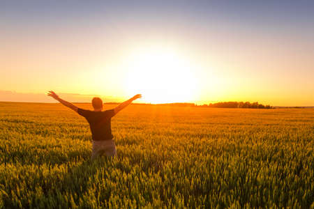 A man with his hands raised up against the backdrop of a sunset or dawn in a rye field. The concept of success, happiness, active lifestyle and outdoor recreation.