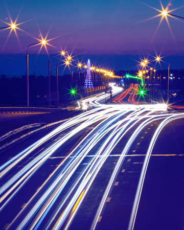 Traces of headlights from cars moving at night on the bridge, illuminated by lanterns. Abstract city landscape with highway at dusk.