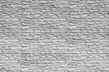 Black and white texture of a wall covered with decorative brick-like tiles. Abstract monochrome background for design.