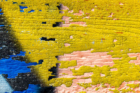 A fragment of colorful graffiti painted on a wooden board with peeling paint close-up. Abstract background for design. 免版税图像