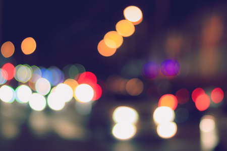 Blurred lights of headlights of cars and lanterns in the night city. Abstract bright bokeh.