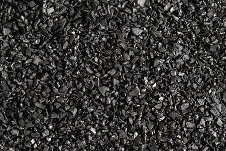 Close-up of black activated carbon texture. Coconut charcoal.