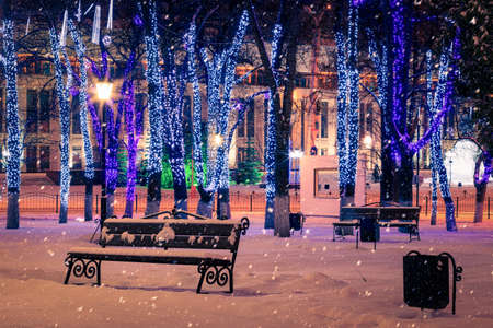 Winter night park with lanterns, benches and Christmas decorations in heavy snowfall.