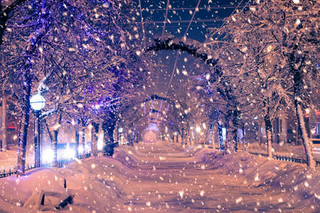 Winter night park with lanterns and Christmas decorations in heavy snowfall.