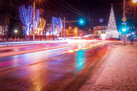 Night city with Christmas decorations, spruce and traces of headlights of moving cars, reflected in the wet asphalt.
