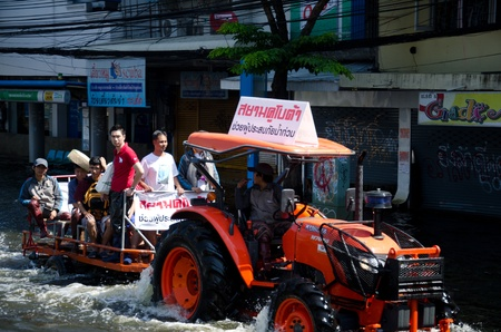 BANGKOK THAILAND – NOVEMBER 13: Truck carries a group of people to evacuate from the flooded area at Phahon Yothin Road during the massive flood crisis on November 13, 2011 in Bangkok, Thailand. Stock Photo - 11201060