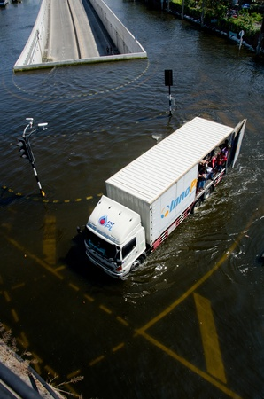 BANGKOK THAILAND � NOVEMBER 13: Truck carries a group of people to evacuate from the flooded area at Phahon Yothin Road during the massive flood crisis on November 13, 2011 in Bangkok, Thailand.