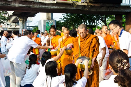 BANGKOK , THAILAND - MARCH 17: People Gives food offerings to a Buddhist monk on March 17, 2012 in Bangkok, Thailand. Thai traditional, people will make merit making by give food to monk
