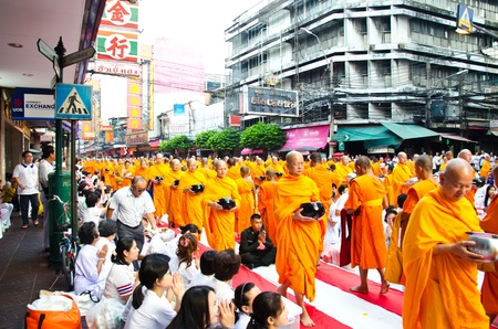 harity event: BANGKOK , THAILAND - MARCH 24: People Gives food offerings to a Buddhist monk on March 24, 2012 Chinatown in Bangkok, Thailand. Thai traditional, people will make merit making by give food to monk. The occasion BuddhaJayanti 2600 years.