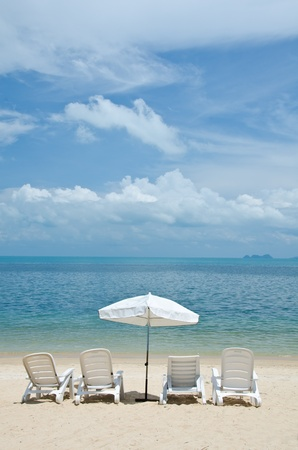 beach chairs and umbrellas on beautiful tropical sand beach photo