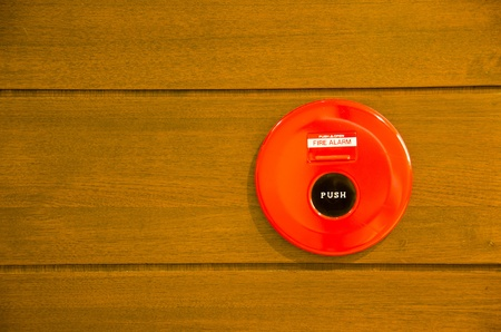 red fire alarm bell set against wood wall photo