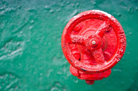 A red wheel valve on a green metal  photo