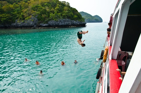 Travellers leap from the deck into the sea. Angthong National Marine Park, Suratthani province, Thailand. Stock Photo - 13365177