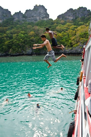 Travellers leap from the deck into the sea. Angthong National Marine Park, Suratthani province, Thailand.