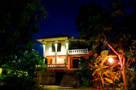 House in the garden at night, light and colorful  photo