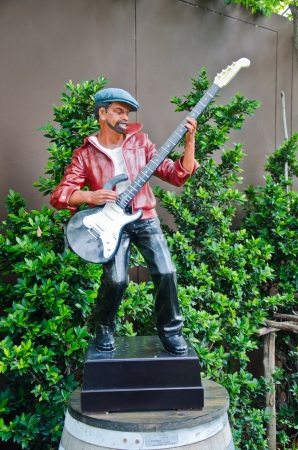 cadence: The man is a statue of the musician playing a guitar  Editorial