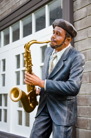 african sax: The man is a statue of the musician blowing a saxophone