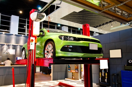 reparations: Car lifted up on the repair stand at garage