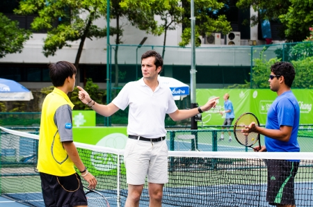 an umpire: BANGKOK - AUGUST 25    Unidentified umpire with player in qualifying singles in ATP Challenger Chang - SAT Bangkok Open 2013 form 24 August - 1 September, 2013 in Bangkok, Thailand  Editorial