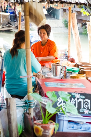 ayothaya: AYUTTHAYA - SEPTEMBER 22   Tourists and people sell food items at Ayothaya Floating Market on September 22, 2013 in Ayutthaya, Thailand  Ayothaya Floating Market  is a very popular tourist attraction
