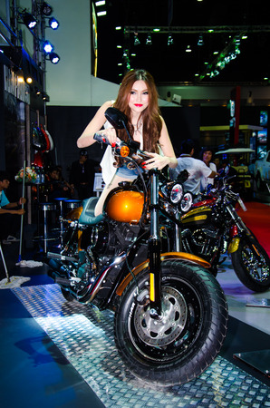 BANGKOK - MARCH 25: Unidentified model with Harley-Davidson Fat Bob motorbike on display at The 35th Bangkok International Motor Show on March 25, 2014 in Bangkok, Thailand.