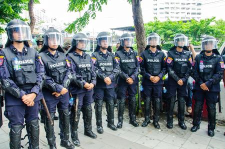 coup: BANGKOK - MAY 24  Riot police stand guard on Major Cineplex Ratchayothin Bangkok during a violent anti-Military coup on May 24, 2014 in Bangkok, Thailand
