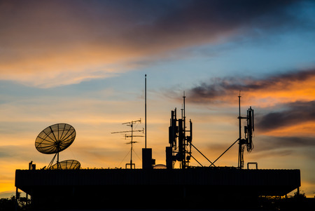 Satellite dish and Telecom tower in twilight at sunset.