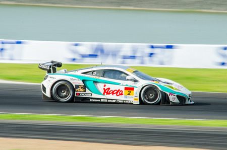 buriram: BURIRAM - OCTOBER 5: Kazuho Takahashi and Hiroki Katoh with SYNTIUM Apple MP4-12C on display at The 2014 Autobacs Super GT Series Race 7 on October 5, 2014 at Chang International Racing Circuit, Buriram Thailand.