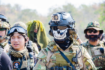 commands: SUPANBURI - FEBRUARY 7 : Airsoft team member in during action await commands befor start mission to protect the stronghold at mission of Black Box Down 2, February 7, 2015, Supanburi, Thailand.