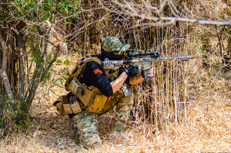 stronghold: SUPANBURI - FEBRUARY 7 : Airsoft team member in during action hiding in the bushes to protect the stronghold at mission of Black Box Down 2, February 7, 2015, Supanburi, Thailand.