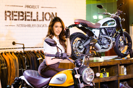 scrambler: BANGKOK - AUGUST 1 : Unidentified model with Ducati Scrambler motorcycle on display at Bangkok International Grand Motor Sale 2015 Big Motor Sale 2015 is exhibition of vehicles for sale on August 1, 2015 in Bangkok, Thailand.