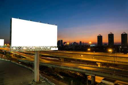 Advertising blank billboard on sidelines of expressway at twilight for advertisement. Stock Photo