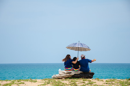 umbella: A young couple and their daughter are taking a selfie at the beach.