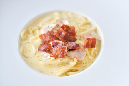 Spaghetti Carbonara with crispy bacon on white plate. Italian cuisine. Stock Photo