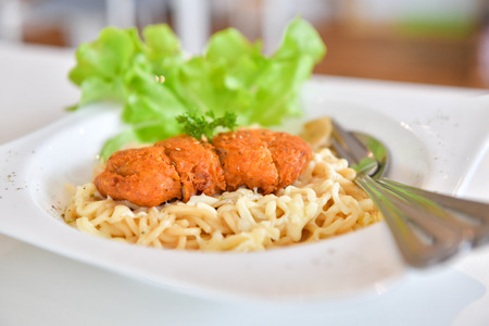 Spaghetti with spicy fried chicken on white plate. Italian cuisine. Stock Photo
