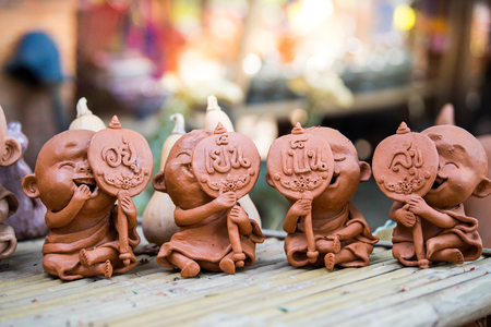 Clay dolls on bamboo table.