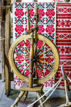 Ancient wooden spinning wheel on the background of a ethnic patterns for embroidery stitch in red and black