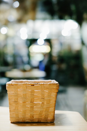 Empty wooden basket on the table with abstract blurred background of resturant lights